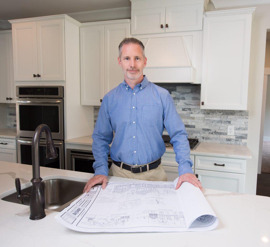 Man Holding Blueprint for a Custom Home