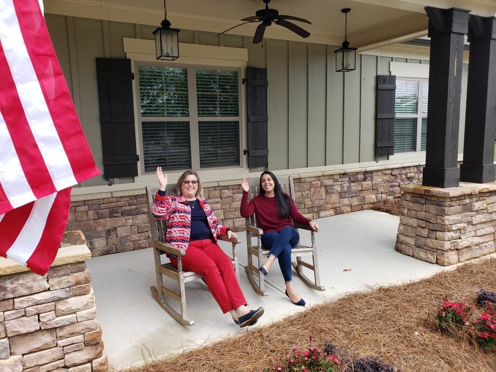 Friendly Traditions of Braselton staff waving while sitting on porch
