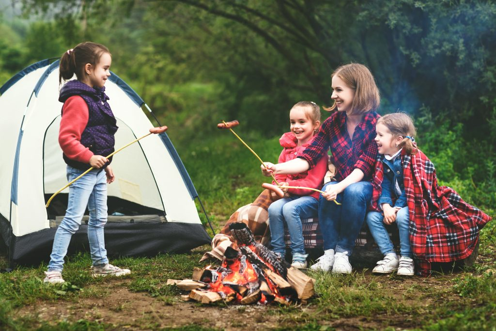 family partaking in outdoor activities, including a bonfire and camping